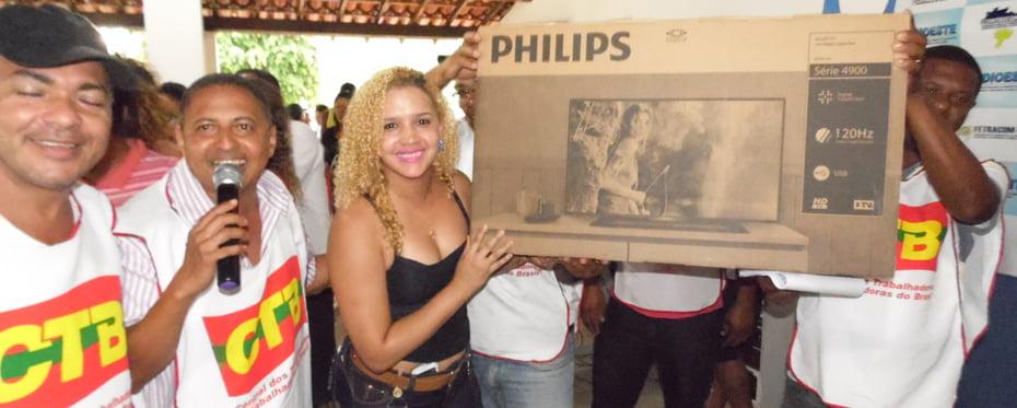 Filha de um trabalhador recebendo o prêmio ganho no sorteio | Foto: Osmar Ribeiro/Falabarreiras